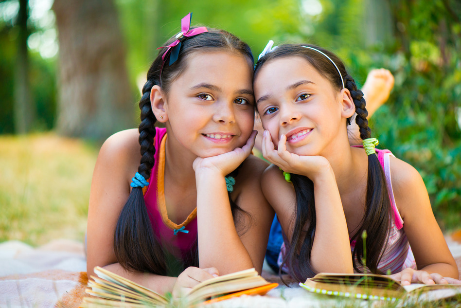 Portrait of two happy hispanic sisters reading in the park